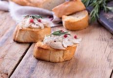 Toasten Sie Brot mit Hühnerpastete auf hölzernem Schreibtisch Stockfoto