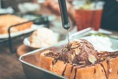 Toasten Sie Brot mit SchokoladenEiscreme in der Platte auf Holztisch lizenzfreie stockfotos