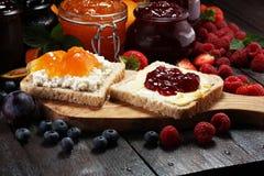 Toasten Sie Brot mit selbst gemachter Erdbeermarmelade und Aprikosenmarmelade O Stockbild