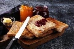 Toasten Sie Brot mit selbst gemachter Erdbeermarmelade und Orangenmarmelade an Lizenzfreie Stockbilder