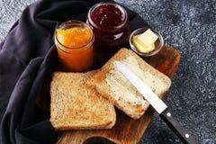 Toasten Sie Brot mit selbst gemachter Erdbeermarmelade und Orangenmarmelade an Stockbild