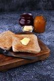 Toasten Sie Brot mit selbst gemachter Erdbeermarmelade und Orangenmarmelade an Stockfotografie