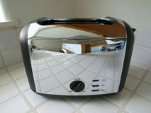 Toaster with Kitchen Reflection. Toaster reflecting a bright, clean condo kitchen Stock Photo
