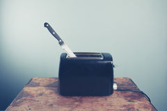 Toaster with knife in it Stock Photo