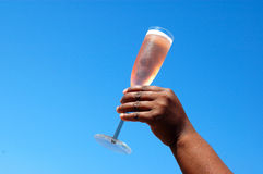 Toasting. An African American black female hand holding a champagne glass with rose sparkling wine in front of blue sky background Stock Photo