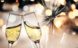 Toasting with champagne glasses against holiday lights and new y. Toasting with champagne lasses against holiday lights and new year fireworks royalty free stock image