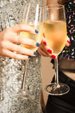 Toasting with champagne. Hands of two girls toasting with champagne at party Royalty Free Stock Image