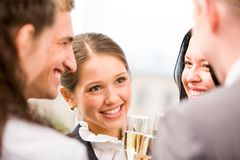 Toasting female. Photo of happy woman holding flute with champagne and smiling at her colleagues during party Stock Photo