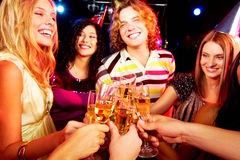 Toasting friends. Portrait of group of happy young people toasting at party Stock Photography