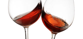 Toasting gesture red and rosé wine with splash, cheers close up with wine isolated. Toasting gesture with red and rosé wine with splash, cheers close up with Royalty Free Stock Image