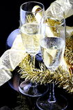 Toasting the New Year. Glasses of champagne with bottle on black background with decorations Stock Image