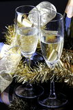Toasting the New Year. Glasses of sparkling wine with bottles on a black background with decorations Stock Image