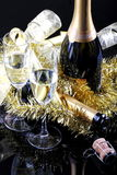 Toasting the New Year. Glasses of sparkling wine with bottles on a black background with decorations Royalty Free Stock Photos
