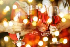 Toasting red wine with light bokeh. Group of hands toasting glasses of red wine for Christmas or xmas celebrating party. Closeup photo with bokeh light for New Stock Photography