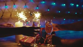 Toasting sparkling champagne two glasses with sparklers on Christmas background. Toasting sparkling champagne two glasses with sparklers over Christmas bokeh stock video