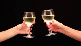 Toasting. Two female hands toasting with white wine on black background, close up stock video footage
