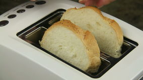 Toasting White Bread. Two slices of bread put in a toaster and then toasted stock video footage
