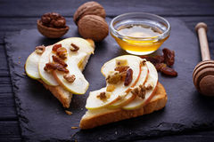 Toasts with apple, walnuts, raisin and honey. Selective focus Stock Photos