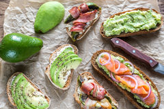 Toasts with avocado and different toppings Stock Image