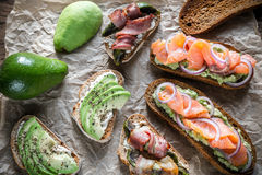 Toasts with avocado and different toppings Stock Photography