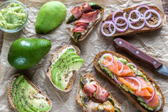 Toasts with avocado and different toppings Stock Photo