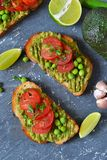 Toasts with avocado, green peas and tomatoes royalty free stock photography