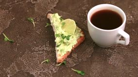Toasts with avocado pate, fresh microgreen and cup of coffee on dark concrete background stock video
