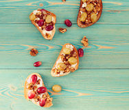 Toasts with baked grape and ricotta on blue wooden table. Toasts with baked grape, walnut and ricotta on blue wooden table Stock Photos