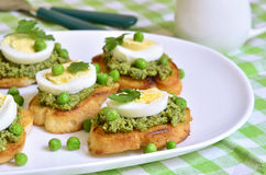 Toasts with basil pesto,eggs and green peas. Stock Photo