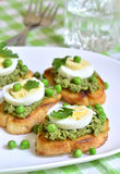 Toasts with basil pesto,eggs and green peas. Stock Images