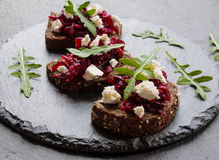 Toasts with beet and cheese on the dark stone background. Toasts on the dark stone background. Cheese, beet and arugula Stock Photo