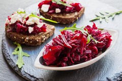 Toasts with beet and cheese on the dark stone background. Toasts on the dark stone background. Cheese, beet and arugula Royalty Free Stock Images