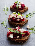Toasts with beet and cheese on the dark stone background. Toasts on the dark stone background. Cheese, beet and arugula Royalty Free Stock Photography