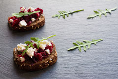 Toasts with beet and cheese on the dark stone background. Toasts on the dark stone background. Cheese, beet and arugula Stock Image