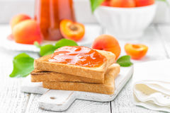 Toasts of bread with apricot jam and fresh fruit with leaves on white wooden table. Tasty breakfast. Royalty Free Stock Images