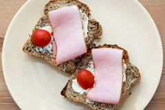 Toasts with butter, ham and cherry tomatoes Stock Photography