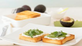 Toasts with cheese and avocado with rucola. Royalty Free Stock Photography