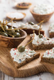 Toasts with cheese pate and capers on a wooden board, vertical Stock Image