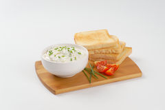 Toasts and chives spread. Stack of fresh toasts and bowl of chives spread on wooden cutting board Stock Images