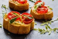 Toasts (Crostini) with ricotta, cherry tomatoes and arugula. On black background Stock Photo