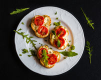 Toasts (Crostini) with ricotta, cherry tomatoes and arugula. On black background Stock Images