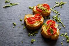 Toasts (Crostini) with ricotta, cherry tomatoes and arugula. On black background Stock Photography