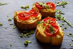 Toasts (Crostini) with ricotta, cherry tomatoes and arugula. On black background Stock Image