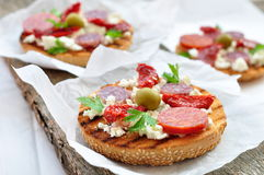 Toasts with dried tomatoes, pepperoni and ricotta Stock Image
