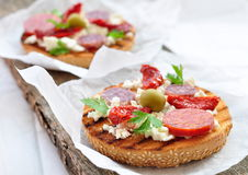 Toasts with dried tomatoes, pepperoni and ricotta Royalty Free Stock Image