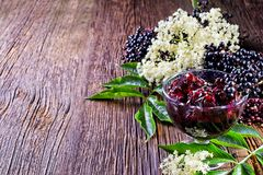 Toasts with elderberry jam and fresh berry fruits on wooden table. Stock Image