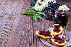 Toasts with elderberry jam and fresh berry fruits on wooden table. Free space for your text. Royalty Free Stock Photography