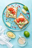 Toasts with feta cheese, tomatoes, avocado, pomegranate, pumpkin seeds and flaxseed sprouts. Diet breakfast. Delicious and healthy royalty free stock image
