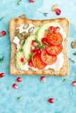 Toasts with feta cheese, tomatoes, avocado, pomegranate, pumpkin seeds and flaxseed sprouts. Diet breakfast. Delicious and healthy royalty free stock photo