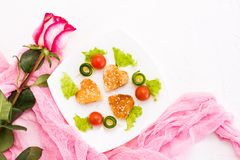 Toasts in the form of heart, cherry and cucumber on a plate. Dish served for lovers and rose. Top view Royalty Free Stock Image